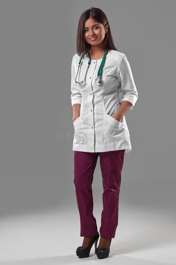 一件医疗长袍的美丽的年轻医生有听诊器的 免版税图库摄影
