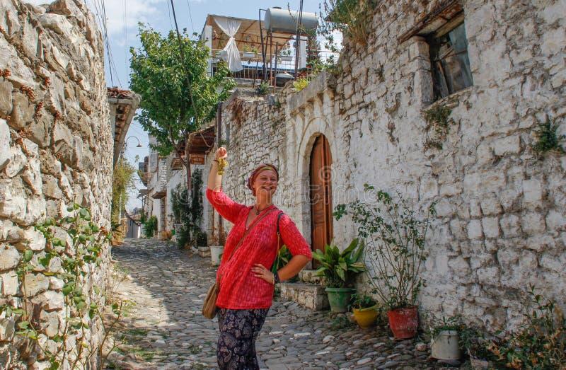 一件桃红色女衬衫的一个年轻旅游女孩在一条被修补的路站立在培拉特古老阿尔巴尼亚镇,俯视medieva 库存图片