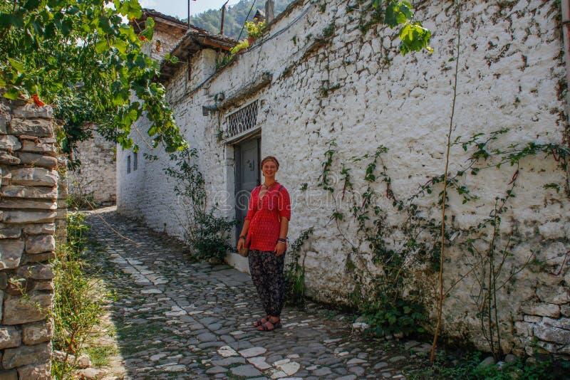 一件桃红色女衬衫的少女游人在一条被修补的路站立在培拉特古老阿尔巴尼亚  免版税图库摄影