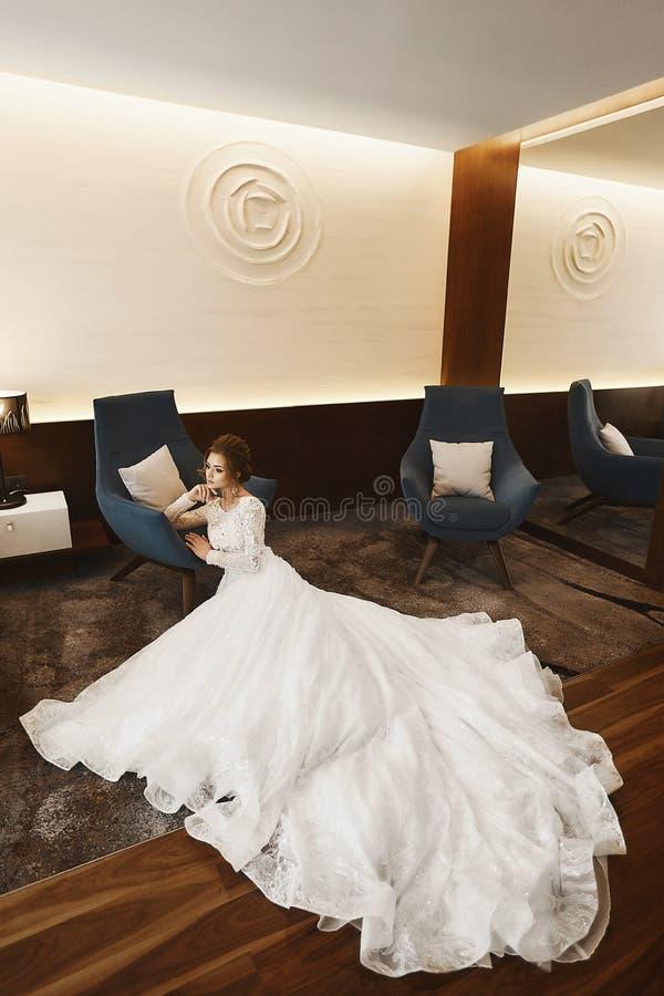 一件时兴的鞋带礼服的典雅和美丽的式样女孩有裸体后面的坐地板在豪华内部 免版税图库摄影