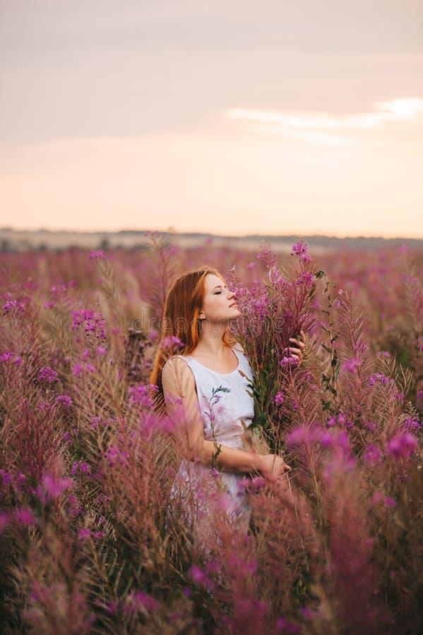 一件礼服的美丽的红发女孩在杨柳茶的一块花田 免版税库存图片
