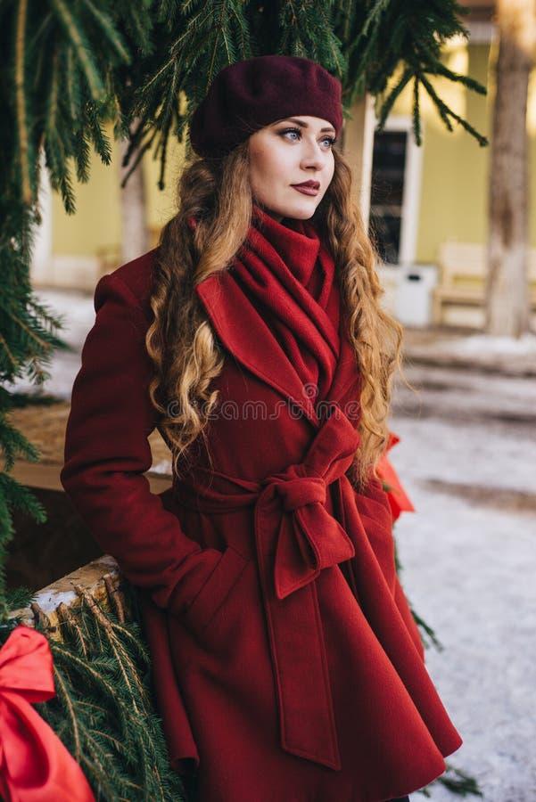一件红色外套和贝雷帽的一美女沿圣诞节街道走 免版税库存图片