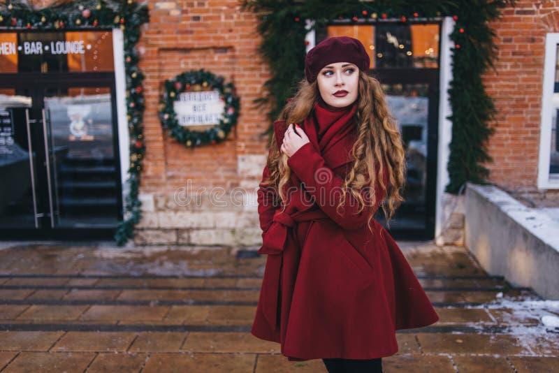 一件红色外套和贝雷帽的一美女沿圣诞节街道走 免版税库存照片