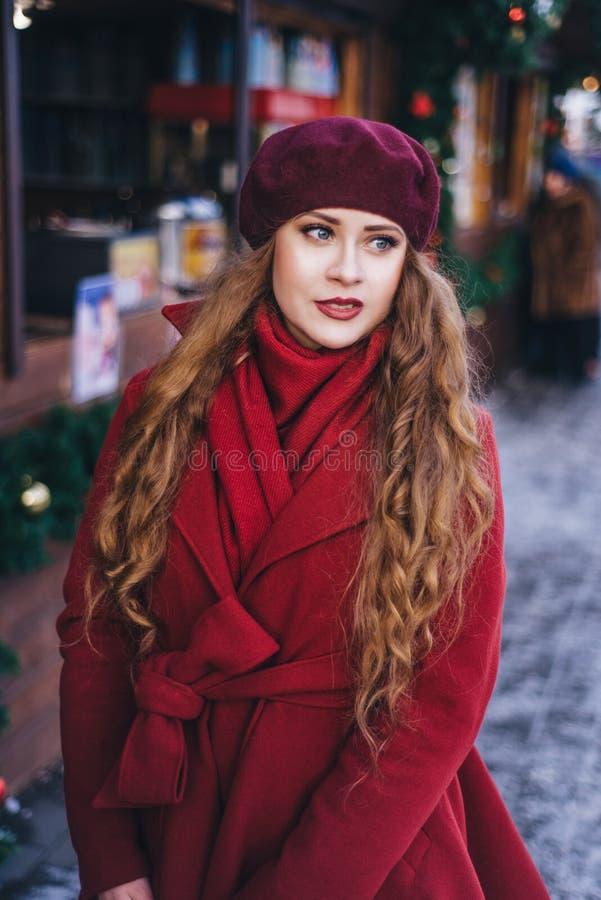 一件红色外套和贝雷帽的一美女沿圣诞节街道走 库存图片