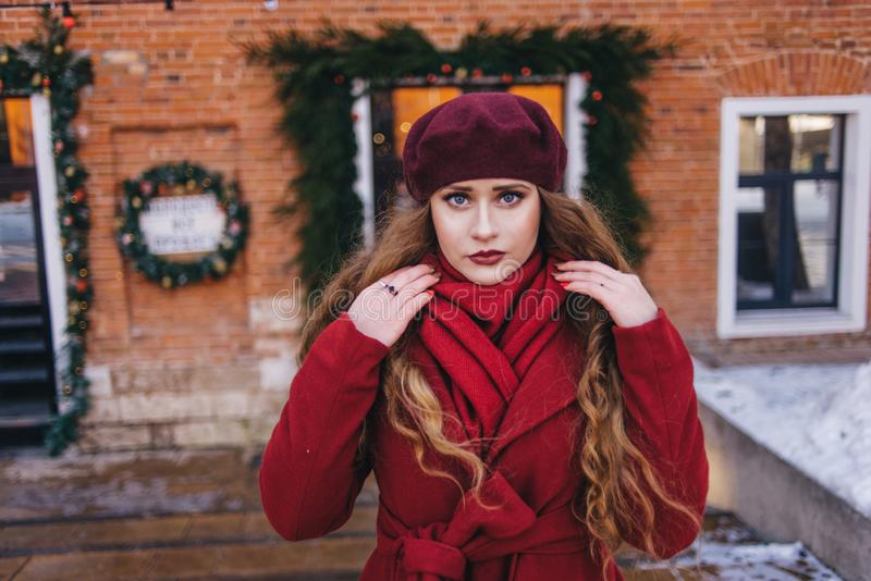 一件红色外套和贝雷帽的一美女沿圣诞节街道走 库存照片