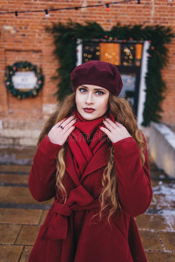 一件红色外套和贝雷帽的一美女沿圣诞节街道走 免版税图库摄影