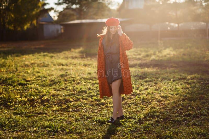 一件红色贝雷帽和橙色外套的十六岁的微笑的青少年的女孩在直接阳光下户外 免版税库存照片