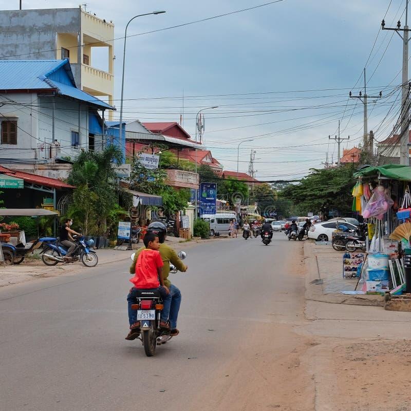 一件红色T恤杉的男孩穿过城市,亚洲贫民窟乘坐滑行车 库存照片