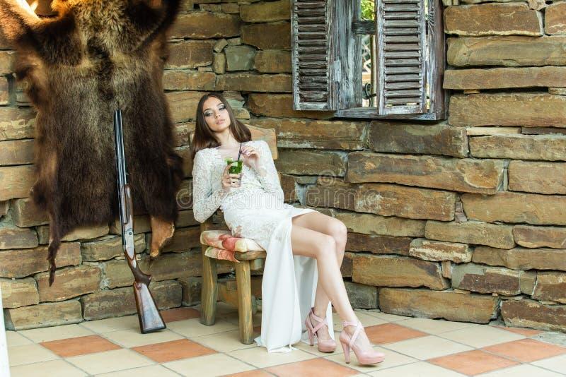 一件白色礼服的美女喝着坐在一杆寻找的步枪旁边的mojito 库存照片