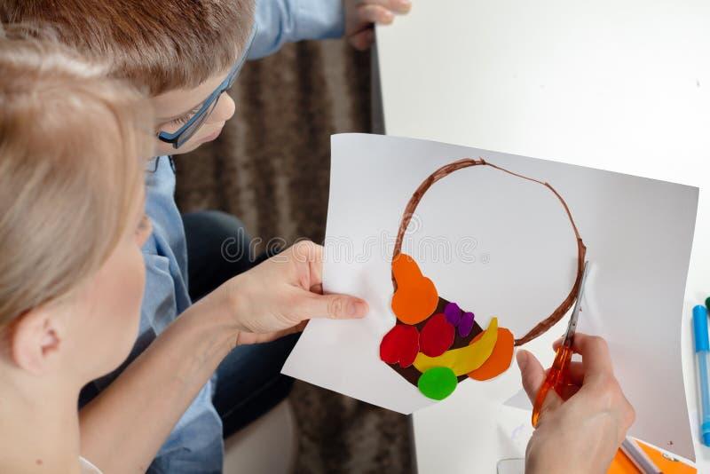 一件蓝色衬衣的男孩有妈咪的 男孩的妈妈裁减剪与孩子完成的塑料工作 图库摄影