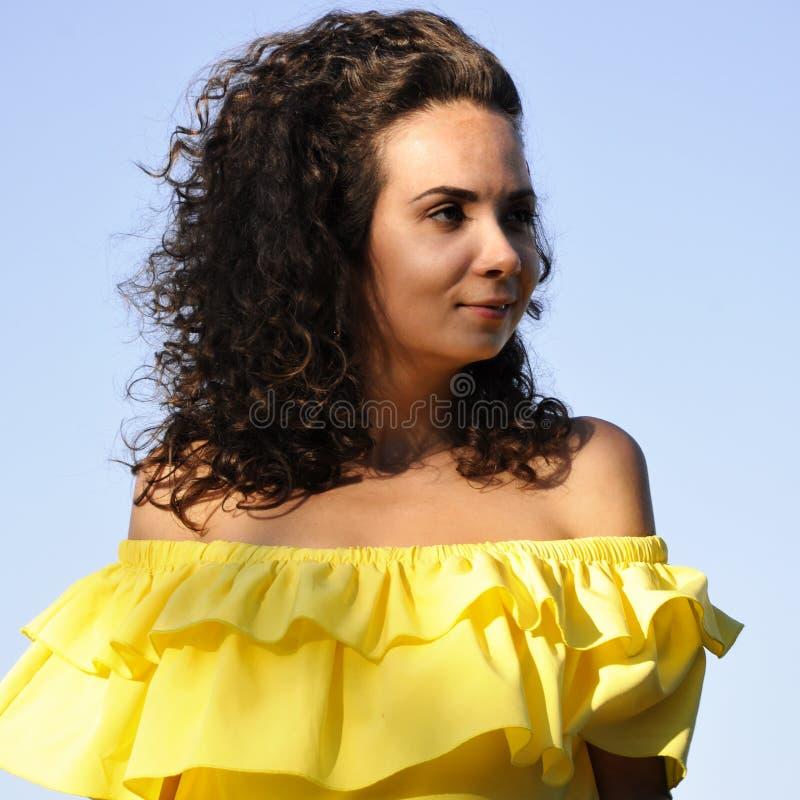 一件黄色礼服的年轻愉快的卷曲深色头发的女孩有光秃的肩膀的 免版税图库摄影