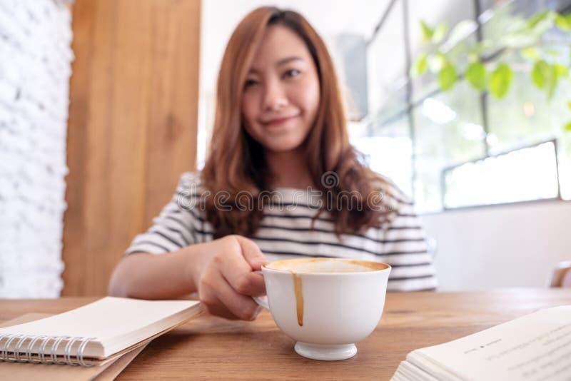 一份美丽的亚裔妇女饮用的咖啡,当学会和看书时 免版税库存图片