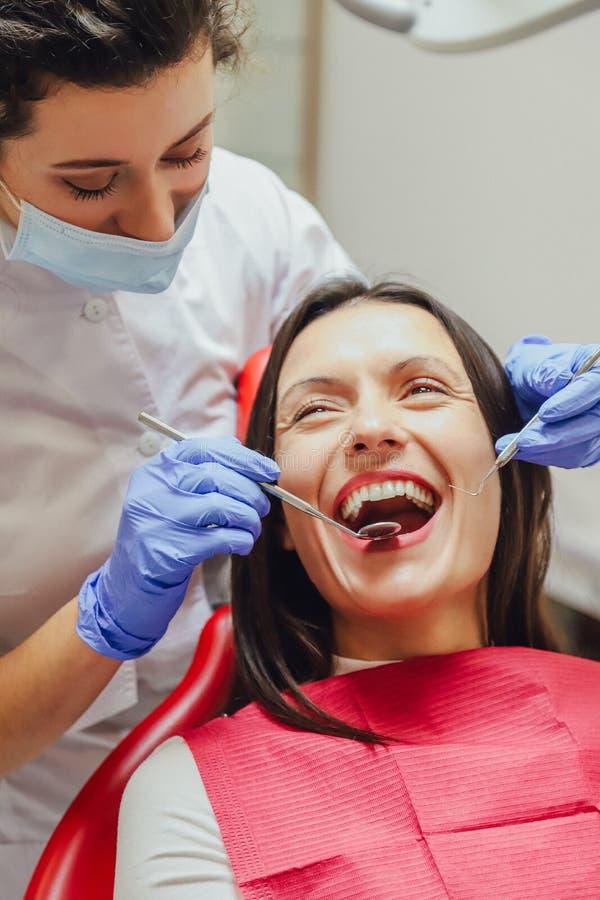一位年轻女性医生在面具和医疗手套打扮 在此期间,患者接受医疗镜子和a 图库摄影