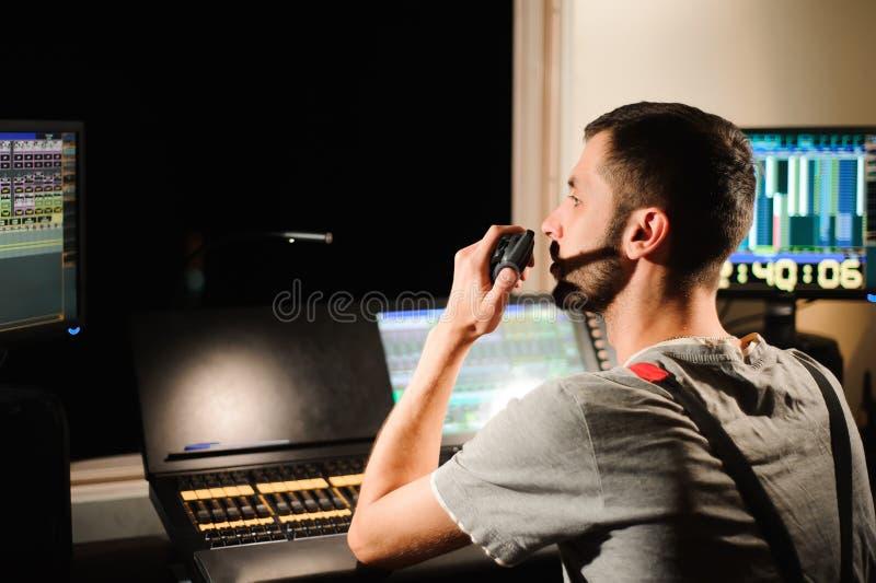 一位灯光师与光在音乐会展示的技术员控制一起使用 专业轻的搅拌器,混合的控制台 免版税库存图片