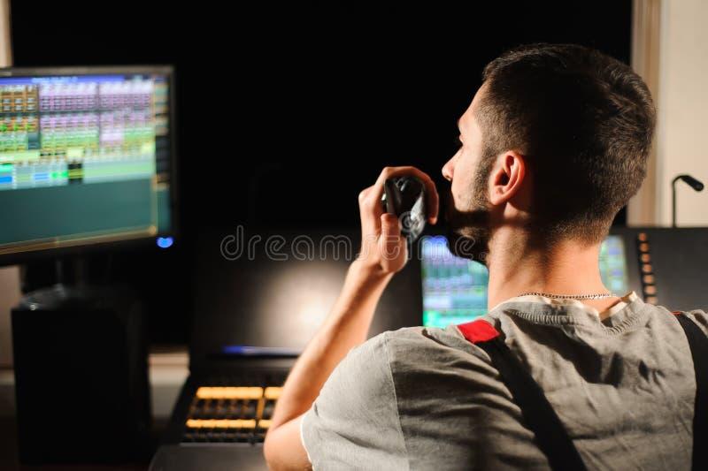 一位灯光师与光在音乐会展示的技术员控制一起使用 专业轻的搅拌器,混合的控制台 图库摄影
