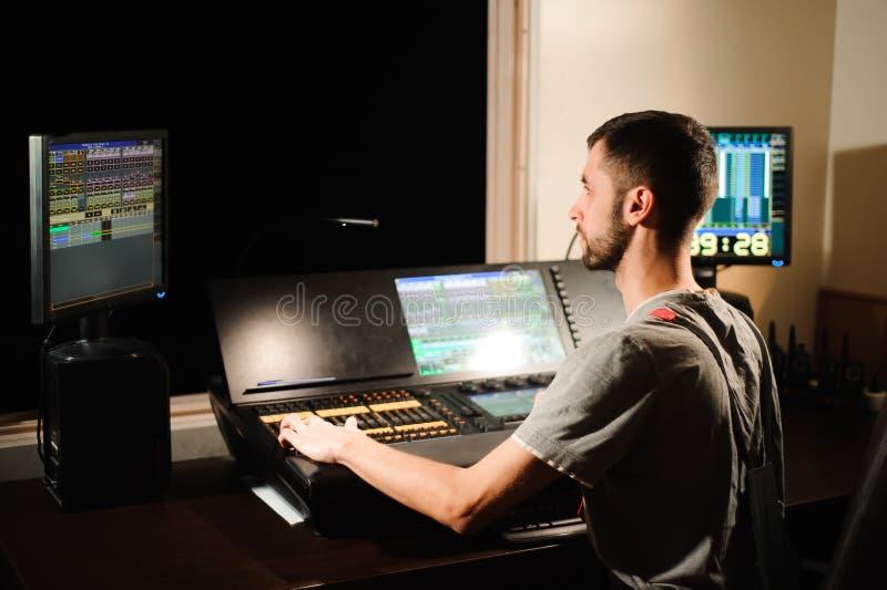 一位灯光师与光在音乐会展示的技术员控制一起使用 专业轻的搅拌器,混合的控制台 库存图片