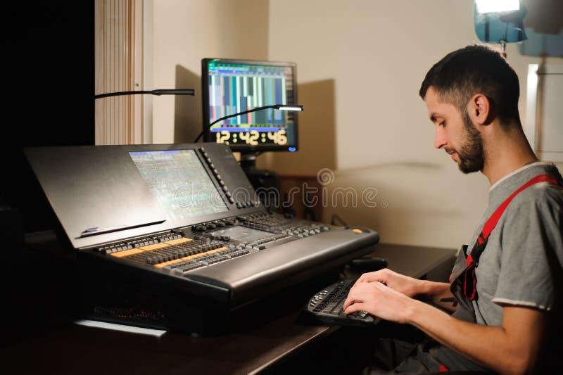 一位灯光师与光在音乐会展示的技术员控制一起使用 专业轻的搅拌器,混合的控制台 免版税库存照片