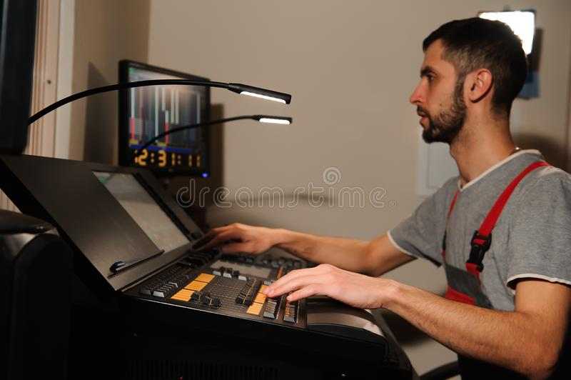 一位灯光师与光在音乐会展示的技术员控制一起使用 专业轻的搅拌器,混合的控制台 免版税图库摄影
