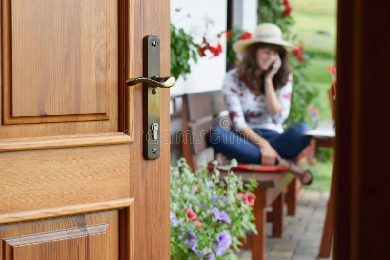 一半开门入年轻女人坐,放松并且打电话的美丽的夏天大阳台和开花的庭院 免版税库存照片