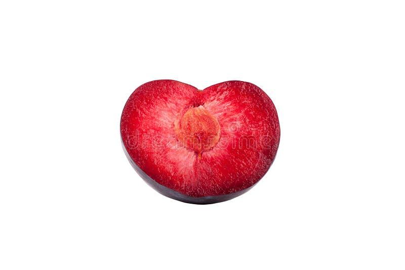 一半在心脏红色里面形状的成熟李子在白色背景被隔绝的关闭的宏指令 免版税库存照片