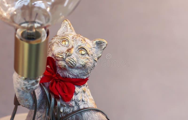 一只猫的古铜色小雕象与灯的 免版税图库摄影