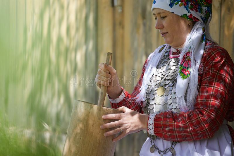 一名妇女在村庄参与家务 女孩运载桶从一个干净的来源的水 库存照片