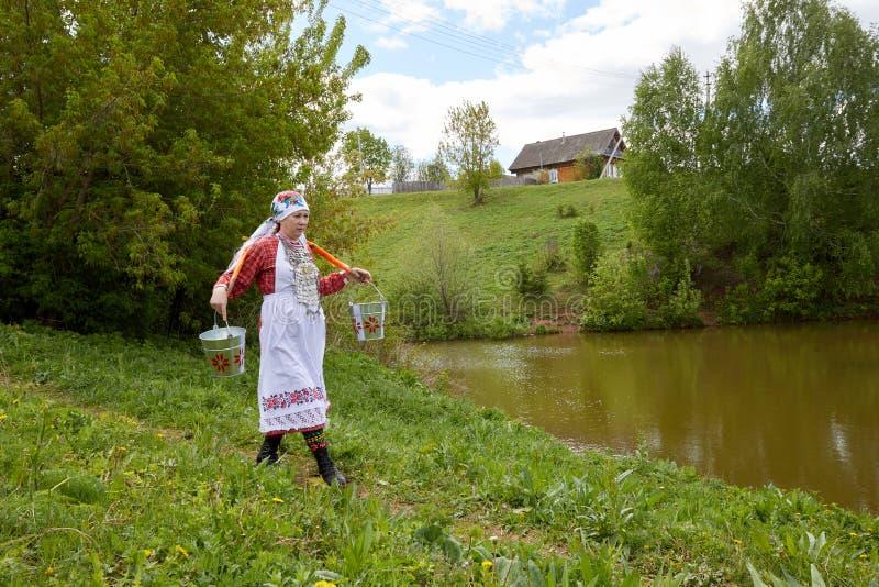 一名妇女在村庄参与家务 女孩运载桶从一个干净的来源的水 图库摄影