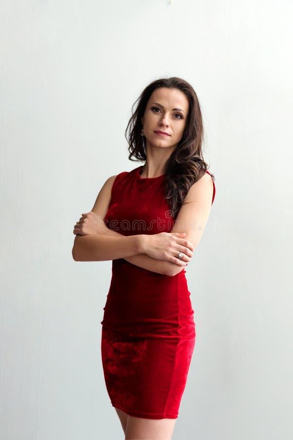 一名年轻可爱的深色的妇女的画象一件短的红色礼服的有在背景的白色墙壁的 免版税库存照片