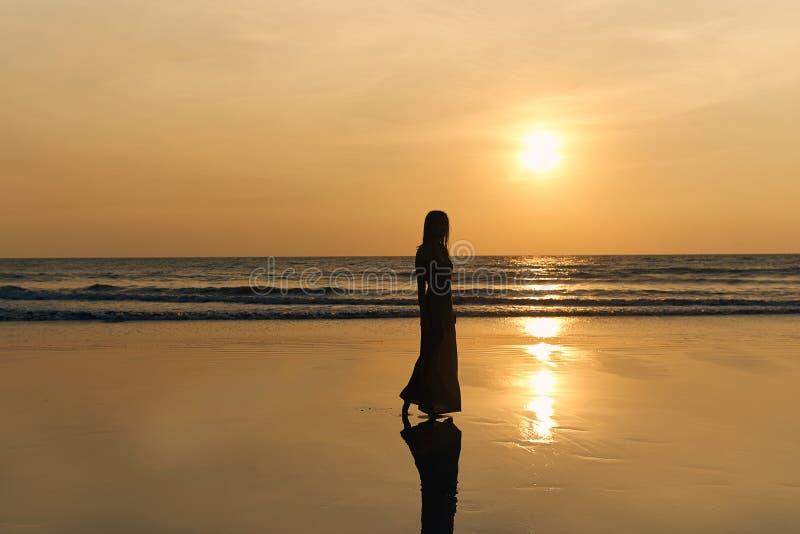 一名年轻苗条妇女的对比剪影以晴朗的日落、海和沙滩为背景的 图库摄影