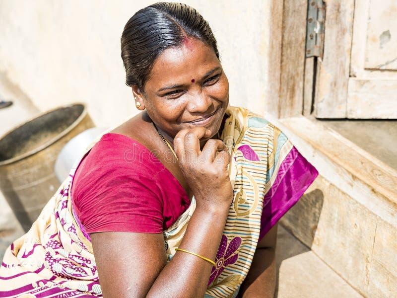 一名愉快的微笑的成熟妇女的画象用在看照相机的下巴的手 美丽的拉丁妇女的接近的面孔有褐色的 库存照片