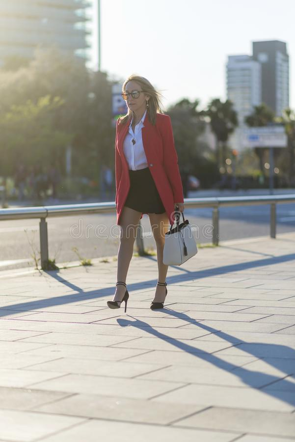一名端庄的妇女佩带的太阳镜、红色夹克,裙子和拿着一个白色提包的侧视图,当走在a时的街道 免版税库存图片