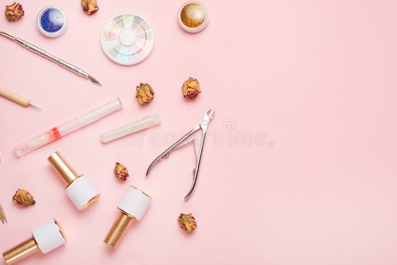 一套为修指甲和修脚的化妆工具在桃红色背景 胶凝体擦亮剂、指甲锉和少年和顶视图 库存照片