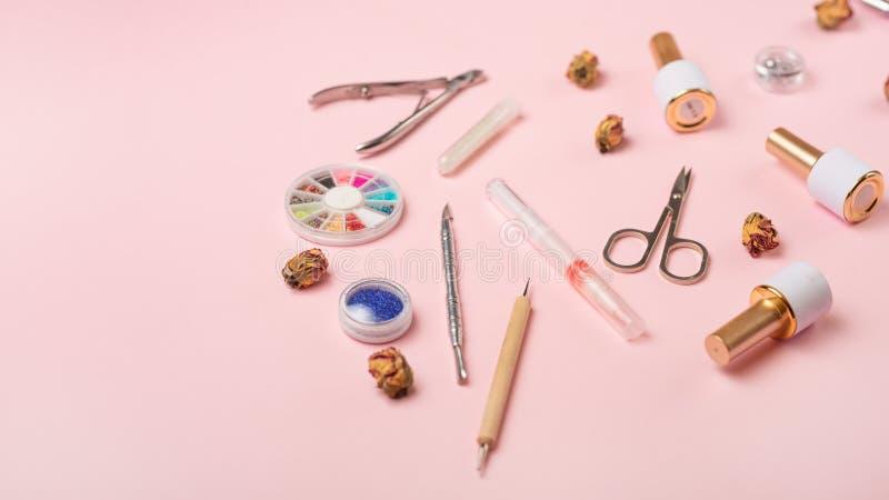 一套为修指甲和修脚的化妆工具在桃红色背景 胶凝体擦亮剂、指甲锉和少年和顶视图 免版税库存照片