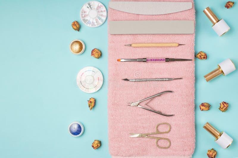 一套为修指甲和修脚的化妆工具在蓝色背景 胶凝体擦亮剂、指甲锉和少年和顶视图 库存照片