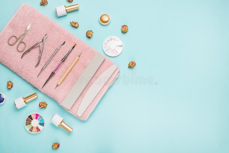 一套为修指甲和修脚的化妆工具在蓝色背景 胶凝体擦亮剂、指甲锉和少年和顶视图 免版税图库摄影