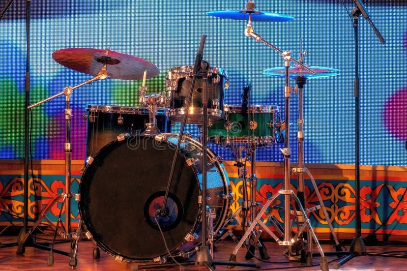 一套在阶段的打击乐器 鼓和板材 机架和话筒 音乐主题 库存照片
