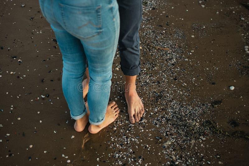一对年轻夫妇获得乐趣并且走在海海岸线 腿关闭  在海滩的浪漫日期 库存图片
