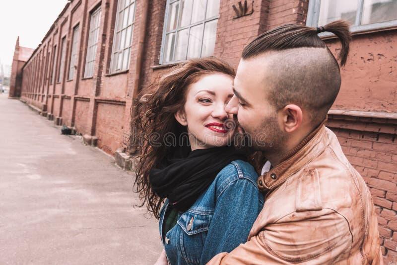 一对愉快的爱恋的夫妇的画象在一个老城市大厦的背景的 免版税库存照片