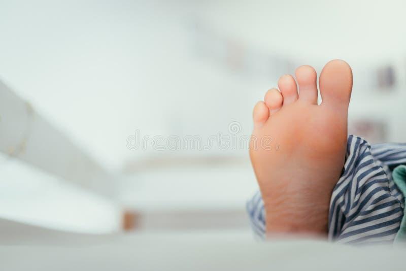 一少女的赤裸脚在床上,早晨 免版税库存图片