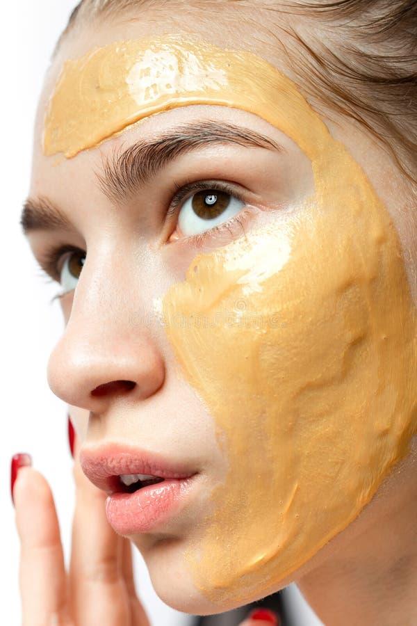 一少女的面孔有黄色化妆面具的对此 库存照片