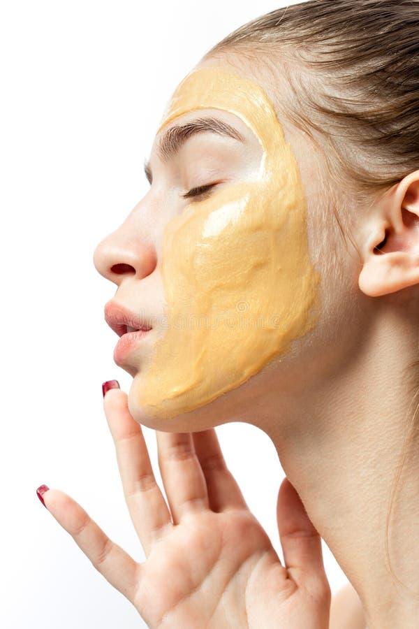 一少女的面孔有黄色化妆面具的对此 免版税库存图片