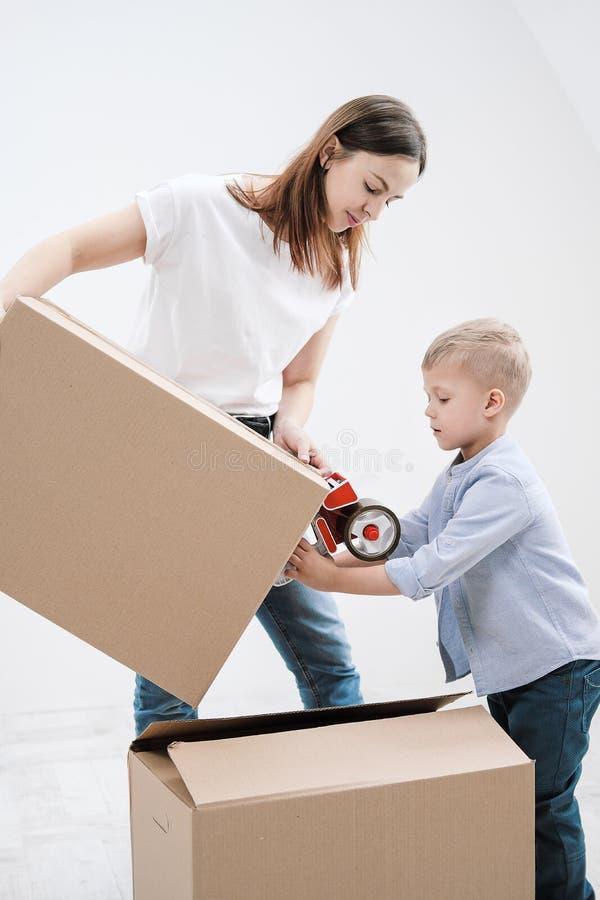 一年轻女人和儿童棍子纸板箱有分配器和橡皮膏的 免版税库存图片