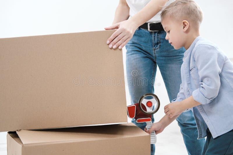 一年轻女人和儿童棍子纸板箱有分配器和橡皮膏的 图库摄影