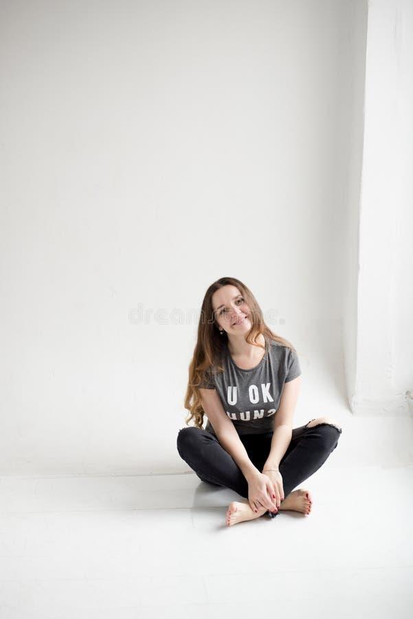 一微笑的少女的画象与盘被隔绝的腿坐白色背景 免版税库存照片
