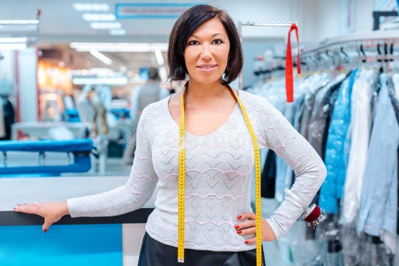 一化工纺织品擦净剂的所有者在她的商店前面的 免版税图库摄影
