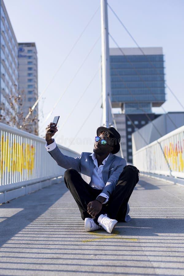 一副年轻非洲黑人佩带的帽子和太阳镜的低角度视图坐地面放松,当采取在晴朗时的一selfie 免版税库存图片