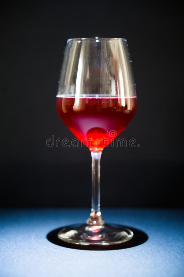 一杯红酒,背景是黑的,坦克从上面照亮与定向光 库存照片