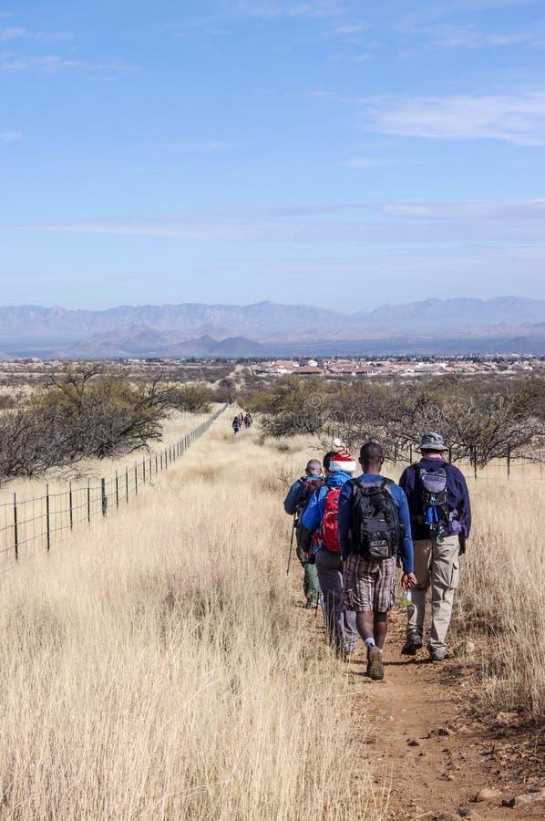 一棵足迹低谷高草和山的徒步旅行者在远的距离 图库摄影