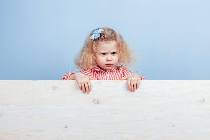 一朵镶边红色和白色礼服和蓝色花的滑稽的矮小的卷曲女孩在她的在木板后的头发立场 免版税库存照片