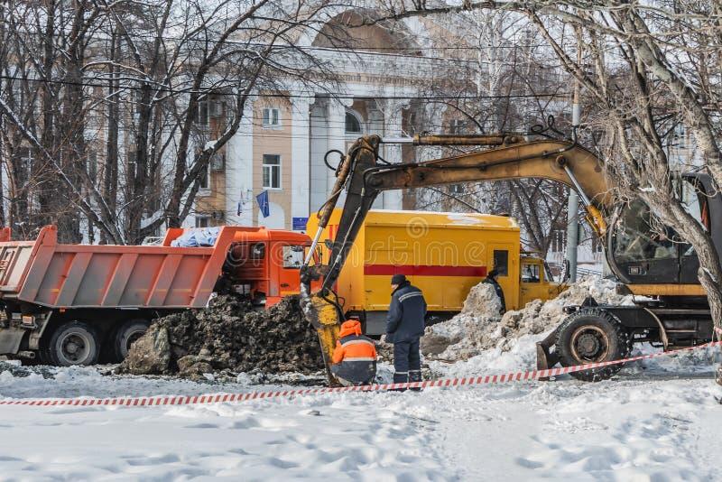 一种黄色挖掘机在城市开掘孔消灭在公共管道的一次事故在冬天 工作者 免版税库存图片